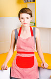 Young house wife on yellow kitchen background