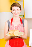 Smiling woman holding fresh loaf of homemade bread