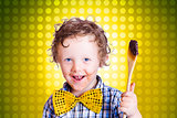 Child holding chocolate covered cooking spoon