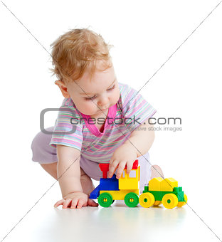 Cute little boy is playing with colorful train isolated on white