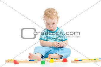 Serious pensive child playing logical education toys isolated on