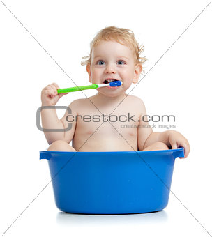 Happy baby kid brushing teeth sitting in basin