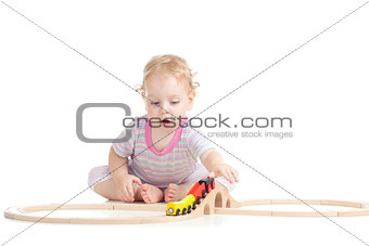 serious cute child is playing with wooden train isolated on whit