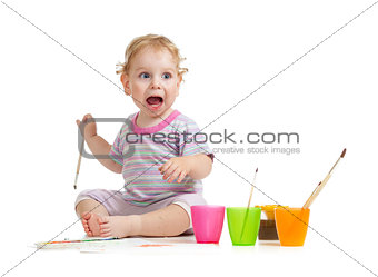 Funny kid with open mouth painting with brush