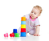 Cute little boy building tower from colorful cups isolated on wh