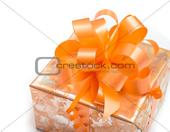 Nice gift packed in paper with orange bow on white background