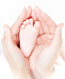Mother&#39;s hands carefully keep baby&#39;s foot with tenderness