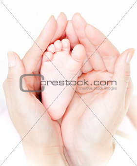 Mother's hands carefully keep baby's foot with tenderness