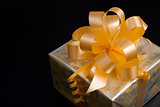 Nice gift packed in golden paper with yellow bow on black backgr