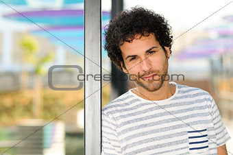 Man with curly hairstyle in urban background