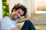 Man with curly hairstyle smiling in urban background