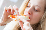 Young happy woman eating of pizza