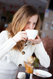 Young beautiful elegant woman drinking coffee or tea