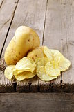 natural potato chips and fresh potato on a wooden background
