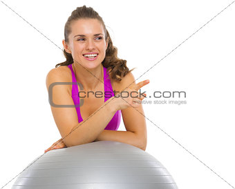 Smiling fitness young woman with fitness ball pointing on copy s