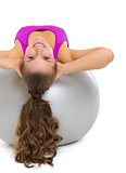 Happy fitness young woman doing abdominal crunch on fitness ball