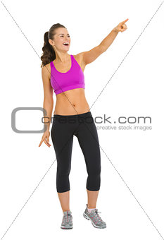 Full length portrait of smiling fitness young woman pointing on