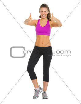 Full length portrait of happy fitness young woman showing thumbs