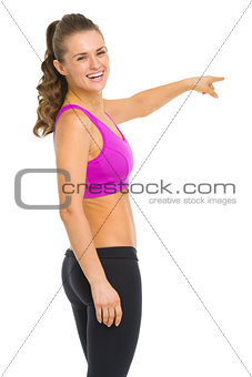 Smiling fitness young woman pointing on copy space