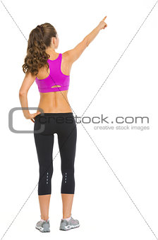 Full length portrait of fitness young woman pointing on copy spa