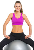 Smiling fitness young woman sitting fitness ball