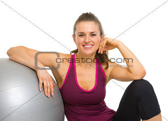 Happy fitness young woman sitting with fitness ball