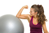 Happy fitness young woman checking biceps