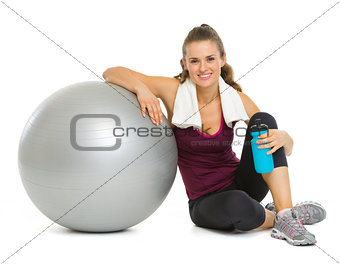 Happy fitness young woman sitting near fitness ball after workou