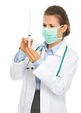 Medical doctor woman in mask with syringe preparing injection