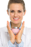 Happy cosmetologist woman showing creme
