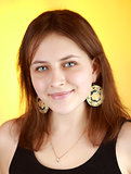Vertical portrait of a girl 17 years of age on a yellow background