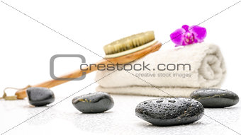 Spa setting with massage stones, brush and a towel