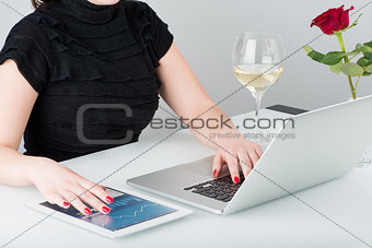 A business woman is working with the laptop and tablet computer.