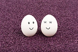 Two smiling eggs on purple sand.