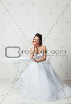 Happy bride sitting in very beautiful dress