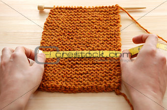 Two hands measuring knitting in inches