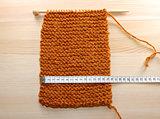 A length of knitting being measured in centimetres