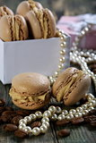 Macaroons in the box, pearls and coffee beans.