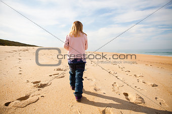 Young girl walking on beach