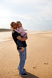 Father holding daughter in arms at the beach