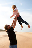 Father throwing daughter in the air at the beach