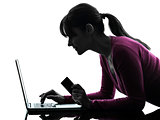 woman holding credit card computing laptop computer silhouette