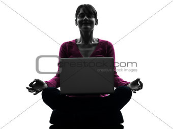 woman sitting in lotus posture computing laptop computer silhoue