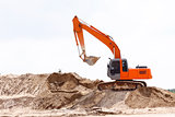 Excavator on sand pile