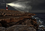 Victorian lighthouse on promontory of rocky cliffs with beam ali