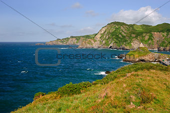 Seaside cliffs with vibrant blue sea and bright sky