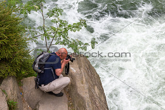man photographing a waterfall