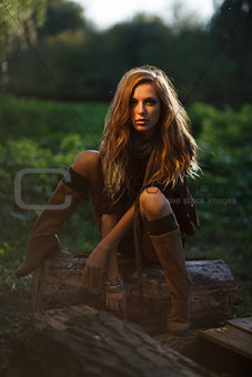 sexy Young Woman sitting on log posing