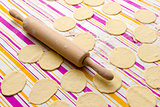 round shape of the dough and rolling pin with flour on the table