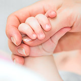 baby holds mother&#39;s finger